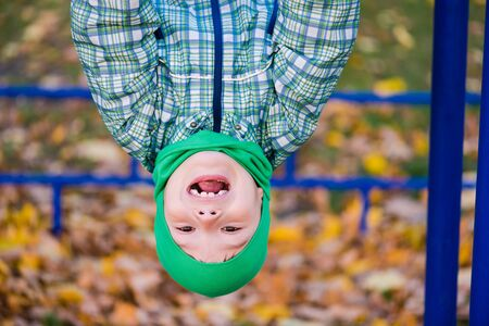Portrait of happy preteen boy upside down