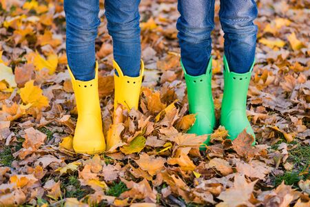 Boy and girl in yellow and green shoes at autumn