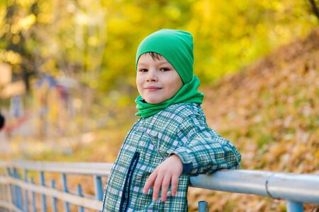 Portrait of cute boy at autumn background