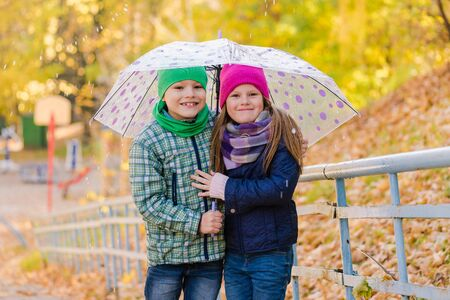 Two kids during autumn rain with umbrella