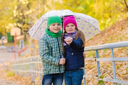 Preteen boy and girl walking at raining park Imagens