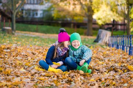 Preteen boy and girl play with yellow foliage 写真素材