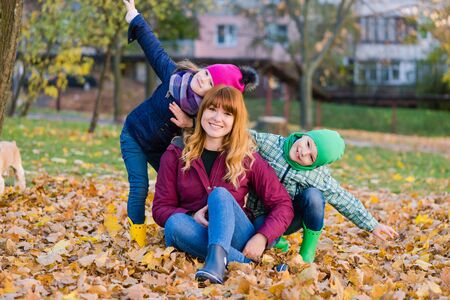 Happy mother with kids during autumn walk 写真素材
