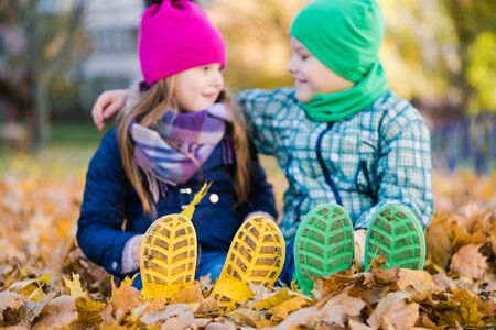 Kids in gumboots sit on autumn leaves