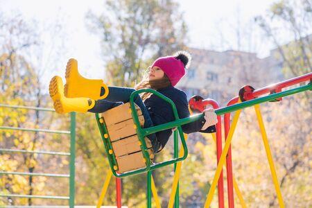 Preteen girl on swing up at sunlight 写真素材