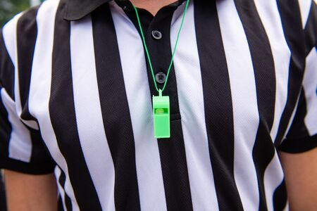 Soccer referee with green plastic whistle. Close-up. Whistle around someone's neck. Archivio Fotografico