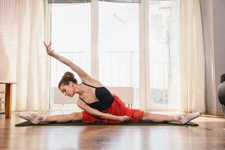 Ballet dancer in twine position on mat