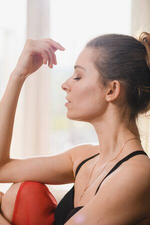 Jolie danseuse de ballet au canapé en tenue de danse professionnelle - justaucorps noir, jupe en mousseline rouge et pointes en satin, avec chignon, look réfléchi à l'isolement à la maison