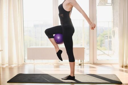 Young sportive woman pinch purple rubber ball by her leg, morning workout indoors during virus epidemy, staying safe and healthy at home