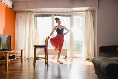 Ballerina in nude pointe shoes, red chiffon skirt, black leotard and hair bun training dance at home isolation