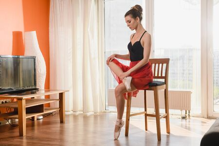 Beautiful ballet dancer sit at home chair