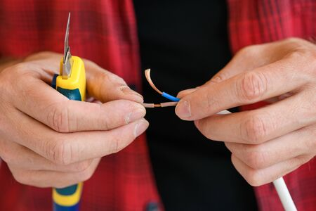 Male hands with knife and electric cables