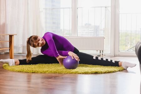 Flexible sportive aged woman pensioner sit at floor in twine split, twist hands with rubber sport ball, morning exercise workout stretching at home 스톡 콘텐츠