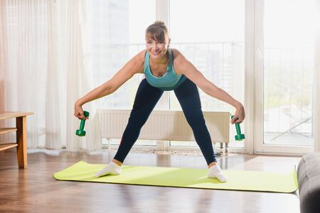 Charming sportive aged woman exercise workout training stretching at home in sportswear, hold dumbbell weights, strengthen hands, pensioner activity 스톡 콘텐츠