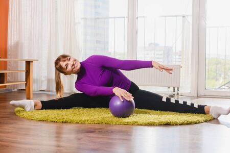 Sportive flexible woman pensioner sit in twine split at home carpet, stretching legs and hands with rubber ball, workout during isolation retirement