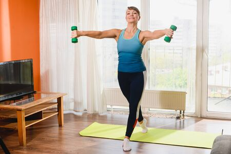 Elderly female pensioner, sportive active lady hold dumbbells, stay at mat, exercise training hands, gymnastics workout during retirement indoors 스톡 콘텐츠