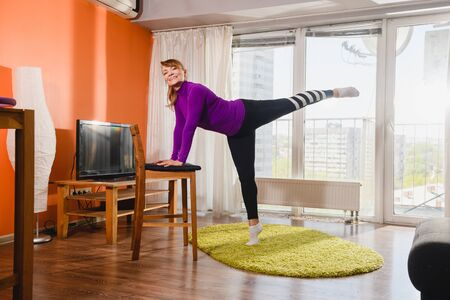 Elderly smiling woman workout exercise stretching at home interior, put hands on chair and raise leg up, wearing sport leggings, isolation gym indoors 스톡 콘텐츠