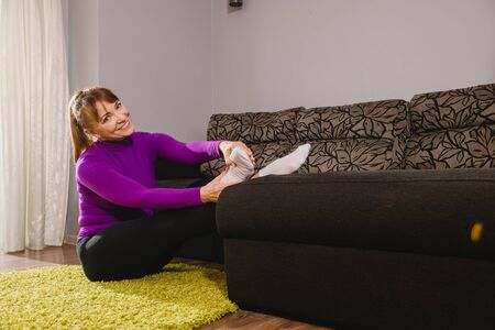 Smiling woman pensioner raise legs up on couch, stretching, exercise, workout at home, retirement isolation activity 스톡 콘텐츠