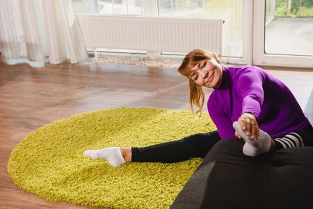 Aged woman pensioner make workout stretching exercise at home sofa and carpet, wearing sport leggings and purple top, active retirement lifestyle