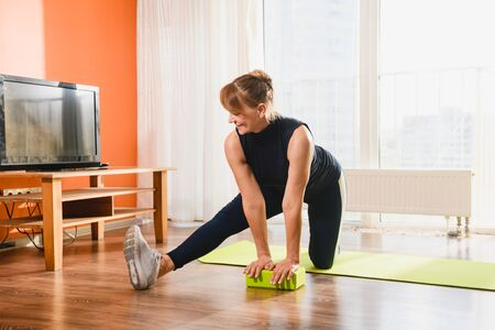 Lady middle age make workout stretching exercise at home interior, using foam plastic brick, training flexibility, healthy lifestyle