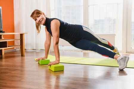 Mature sportive woman exercise at home floor mat, twist legs, using foam plastic bricks blocks, active retirement concept 스톡 콘텐츠