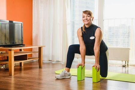 Smiling pensioner woman during morning exercise pose with sport tool - bright foam plastic bricks blocks, retirement healthy lifestyle