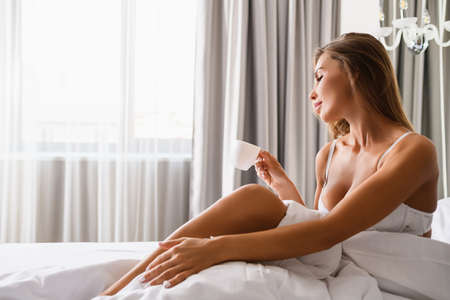 Beautiful female in white bra sit in luxury bed in morning light from window, hold small cup of breakfast drink, sexy model indoors.