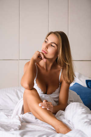 Serious seductive woman wake up and sit in luxurious white bed with naked leg and neckline in lace bra, look at window during beautiful morning with hand on chin, enjoy moment.
