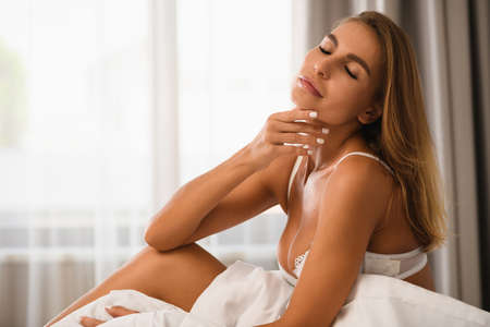 Attractive sexy girl sit in bed with closed eyes, careless chin and neck, wear white bra and blanket in front of window with morning light, luxury lifestyle and leisure. Stock fotó