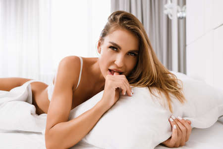 Seductive blonde girl lay in wihte bed, put finger in mouth, hold pillow, look at camera in morning light at luxury home, hotel, appartment background