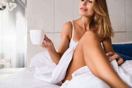Focus on heat from white cup of coffee, tea in hand of sexy lady in bedroom under white blanket indoors, beautiful breakfast in bed of luxury home, hotel.