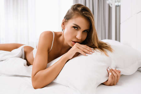 Portrait of seductive blonde woman in white lingerie on beautiful body lie in bed, hug pillow at luxury home, appartment, hotel background, sexy good morning