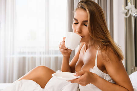 Sexy blonde lady sit in bed in white lace bra, hold white cup and saucer, drinking breakfast hot drink, enjoy morning in sun light at luxury home.