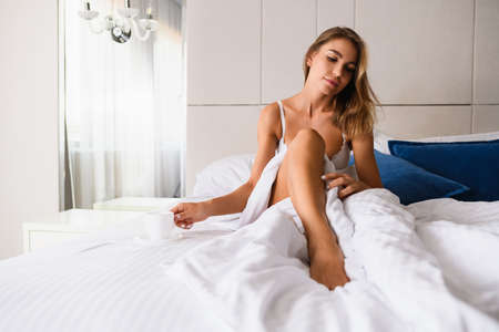 Attractive blonde female in bra with naked leg under blanked have morning coffee, tea, hold cup in hand at luxury room background indoors.