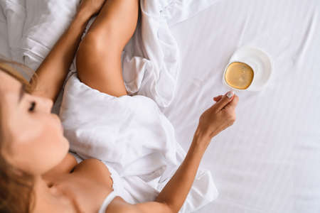 Sexy lady sit in bed, wearing white bra, under blanket with cup of morning breakfast coffee, top view with beautiful leg and breasts indoors.