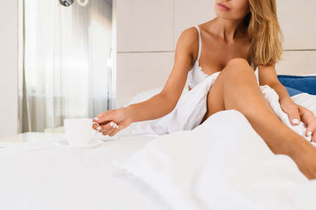 Seductive woman in white lingerie under blanket half face, with sensitive lips and naked leg, take cup of hot coffee, tea from saucer at luxury appartment background.
