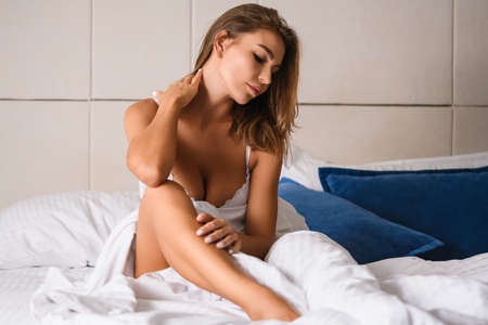 Attractive blond girl with beautiful body sit in white bed with naked leg and neckline, careless herself, enjoy good morning at luxury interior. Stock fotó