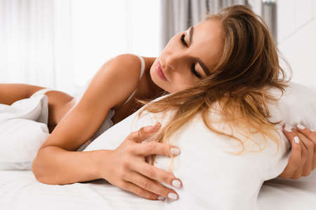Portrait of attractive tender blonde woman put face and hair on pillow in morning light with closed eyes, wearing white bra and panties, sweet sexy dreams concept