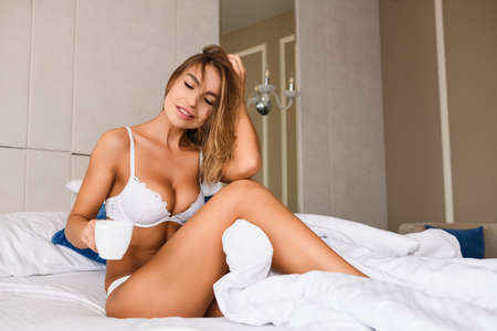 Seductive fit blonde female in white lace underwear sit in bed with white blanket and cup of coffee, tea, luxury home, hotel, appartment bedroom, beautiful morning with sexy lady Stock fotó