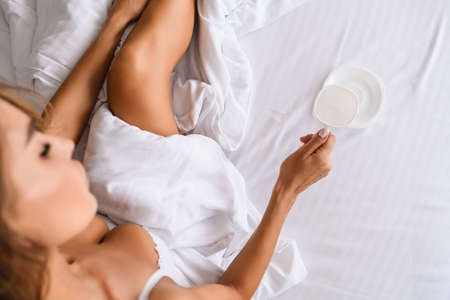 Sexy lady sit in bed, wearing white bra, under blanket with empty cup, top view with beautiful leg and breasts indoors. Stock fotó