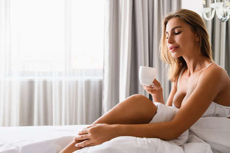 Beautiful female in white bra sit in luxury bed in morning light from window, hold small cup of breakfast drink. Stock fotó