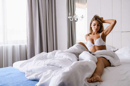 Beautiful young woman sit in morning bed of luxury hotel, appartment with white bed sheets, wear lace lingerie with open window curtains, strething neck, start wonderful day Stock fotó