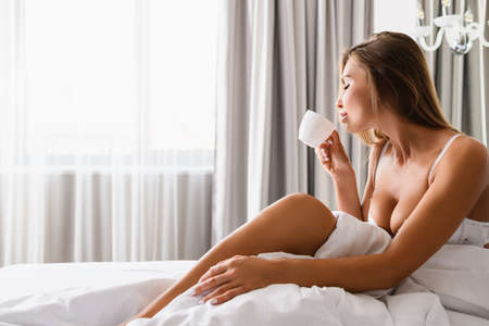 Attractive blonde woman with beautiful body sit in white bra under blanket in light home, hotel bedroom, enjoy morning drink in cup in front of window.