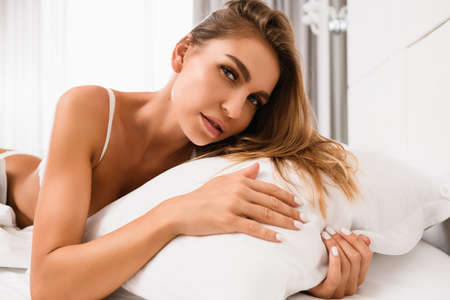 Attractive blonde woman in white bra with sexy neckline lay in luxury appartment, hotel bed, touch white pillow at morning light from window, enjoy beautiful lifestyle indoors Stock fotó