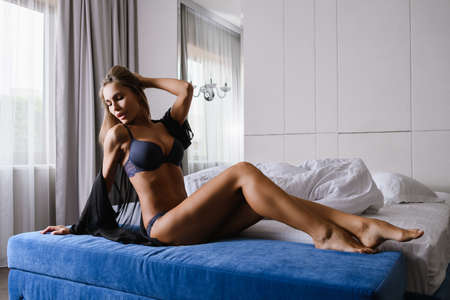 Fit seductive blonde woman sit barefoot at velvet luxury hotel appartment bed, wearing blue panties and bra, beautiful body in chiffon cape, at morning light from window