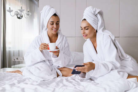 Two females sit at luxury appartment hotel bed at morning with cup, wear bathrobes and towels, look at smartphone, online networking, shopping, chatting, ladies friendship and leisure