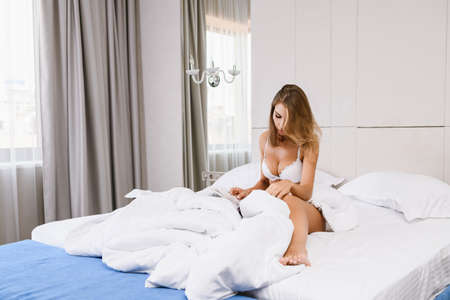 Attractive young female with beautiful body wear white lace bra, covered with blanket at luxury home, room, appartment, hotel in morning light