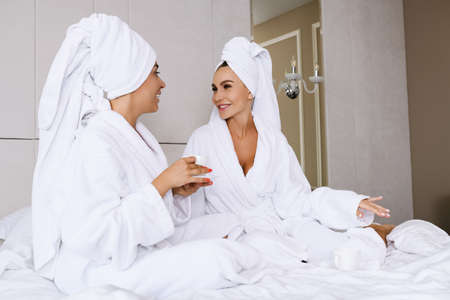 Two smiling and chatting female friends sit in hotel appartment bed with cup, wear head shower towels and bathrobes, plan weekend together at luxury hotel interior Stock fotó