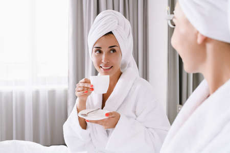 Two women stay in bed of appartment, hotel, have morning breakfast coffee, tea together, wearing head towels and bathrobes, leisure, vacation, luxury lifestyle concept Stock fotó
