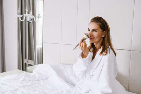 Attractive lady wear white bathrobe, sit in bed, put cosmetics with powder foundation tassel, makeup brush, beautiful morning routine in luxury hotel, home in light tones Stock fotó